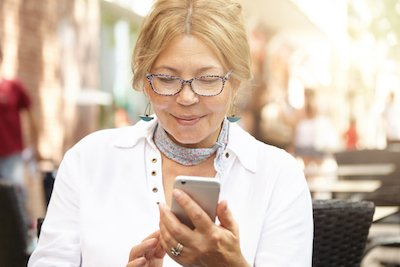 Charming senior woman in spectacles communicating online via social networks while waiting for her old friend, sitting at outdoor cafe, reading message from her son with happy face expression
